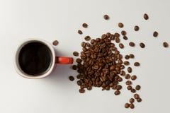 Чашка горячего кофе и кофе фасолей на белой таблице Стоковые Фото