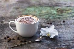 Чашка горячего кофе и орхидея цветут на деревянной предпосылке Традиционное flo орхидеи предпосылки капучино или какао питья дере Стоковые Фото