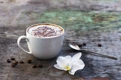 Чашка горячего кофе и орхидея цветут на деревянной предпосылке Традиционное flo орхидеи предпосылки капучино или какао питья дере Стоковые Изображения RF