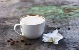 Чашка горячего кофе и орхидея цветут на деревянной предпосылке Традиционное flo орхидеи предпосылки капучино или какао питья дере Стоковая Фотография
