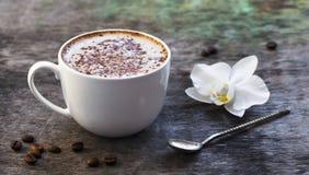 Чашка горячего кофе и орхидея цветут на деревянной предпосылке Традиционное flo орхидеи предпосылки капучино или какао питья дере Стоковое Изображение