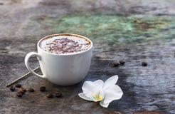 Чашка горячего кофе и орхидея цветут на деревянной предпосылке Традиционное flo орхидеи предпосылки капучино или какао питья дере Стоковая Фотография RF