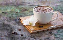 Чашка горячего кофе и орхидея цветут с дневником на деревянной предпосылке Традиционное питье задней части капучино или какао дер Стоковые Изображения RF