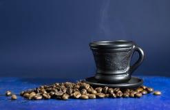 Чашка горячего кофе на старой голубой предпосылке Стоковые Фото