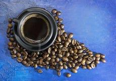 Чашка горячего кофе на старой голубой предпосылке Стоковое Фото