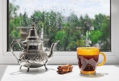 Чашка горячего кофе на windowsill Вне окна дождь Ненастная погода за окном Стоковые Фотографии RF