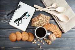 Чашка горячего кофе сортировала с печеньями для завтрака на деревянной винтажной таблице Черные стекла на блокноте Стоковые Фото