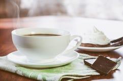 Чашка горячего кофе, частей шоколада и шоколадного торта со сливк яйца белой на деревянном столе стоковое изображение