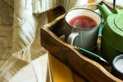 Чашка горячего красного чая плодоовощ, зеленого бака в подносе, свече, связала смертную казнь через повешение на деревянном стуле Стоковые Изображения
