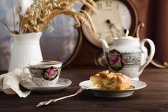 Чашка горячего чая, бака чая и части яблочного пирога на таблице Стоковые Фото
