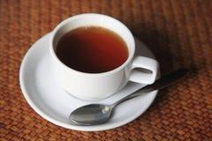 Чашка горячего чая на таблице weave Стоковое фото RF