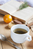 Чашка горячего чая с книгами, печеньями и tangerines на светлом деревянном столе Стоковое фото RF