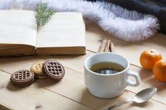 Чашка горячего чая с книгами, печеньями и tangerines на светлом деревянном столе Стоковое Изображение RF