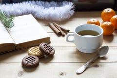 Чашка горячего чая с книгами, печеньями и tangerines на светлом деревянном столе Стоковое Изображение