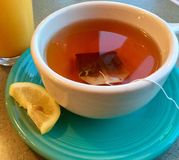 Чашка горячего чая с куском лимона стоковые фото