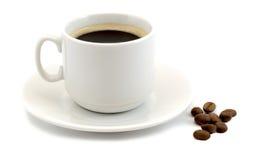 Чашка горячего черного кофе при кофейные зерна изолированные на белой предпосылке Стоковая Фотография