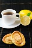 Чашка горячего черного чая, лимона, домодельных печений Стоковые Изображения RF