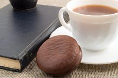 Чашка горячего шоколада, старой книги и печенья на старой скатерти Стоковые Фотографии RF
