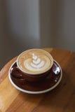 Чашка горячего latte кофе с красивым стилем на деревянной таблице на внутри Стоковое Фото