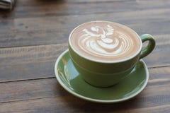 Чашка горячего latte кофе с красивым стилем на деревянной таблице Стоковые Изображения RF
