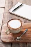 Чашка горячих кофе и блокнота на деревянной предпосылке таблицы Стоковое Фото