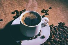 Чашка горячих кофе и поддонника на коричневой таблице Темная предпосылка стоковые изображения rf