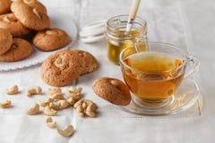 Чашка горячих печений чая и овсяной каши с гайками Стоковая Фотография
