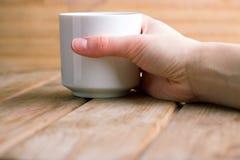 Чашка горячих чая или кофе в руках Стоковое Изображение RF