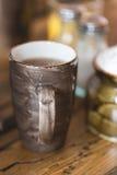 Чашка глины коричневая темноты фильтровала кофе на деревянной деревенской таблице Стоковое Изображение RF