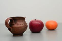 Чашка глины, красное яблоко, мандарин Стоковые Изображения