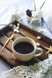 Чашка домодельного какао с зефиром, шоколадом, цветками и smartphone на деревенском деревянном подносе в уютной кровати Стоковое фото RF