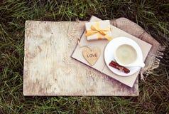 Чашка душистого кофе, книги и деревянного сердца белизна осени изолированная принципиальной схемой Домашний комфорт Стоковые Изображения