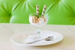 Чашка десерта мороженого на предпосылке зеленого цвета ложки плиты Стоковые Изображения RF
