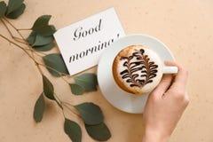 Чашка женщины выпивая ароматичного кофе на таблице Стоковые Изображения