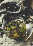 Чашка зеленого чая с лепестками цветка и плодоовощами, винтажным деревянным b стоковые изображения rf
