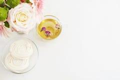 Чашка здорового травяного чая с высушенными розами Красивые свежие цветки, французские печенья меренги на светлой мраморной табли Стоковые Фото