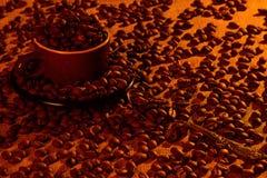 Чашка и ложка вполне кофейных зерен на дерюге Стоковое фото RF