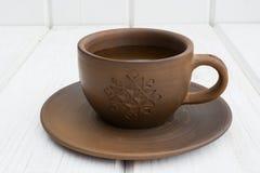 Чашка и поддонник глины чашки и поддонника глины на белой деревянной предпосылке Стоковое фото RF