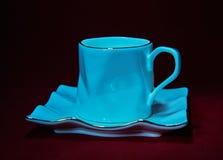 Чашка и поддонник чая фарфора на красной предпосылке Стоковые Фото