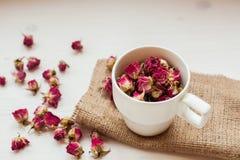 Чашка и сухие розы на таблице стоковые изображения rf