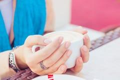 Чашка капучино в женских руках стоковое фото