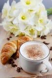 Чашка капучино и круассана с цветками стоковые фото