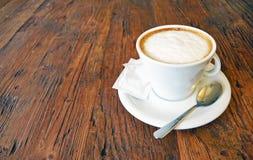 Чашка капучино на предпосылке деревянного стола Стоковая Фотография
