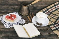 Чашка капучино, сердца сформировала баки сообщения, тетради, карандаша и кофе ширины печений на коричневом деревянном столе стоковые фото