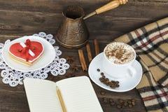 Чашка капучино, сердца сформировала баки сообщения, тетради, карандаша и кофе ширины печений на коричневом деревянном столе стоковое фото rf
