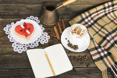 Чашка капучино, сердца сформировала баки сообщения, тетради, карандаша и кофе ширины печений на коричневом деревянном столе стоковая фотография
