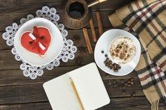 Чашка капучино, сердца сформировала баки сообщения, тетради, карандаша и кофе ширины печений на коричневом деревянном столе стоковое изображение