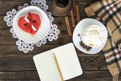 Чашка капучино, сердца сформировала баки сообщения, тетради, карандаша и кофе ширины печений на коричневом деревянном столе стоковое изображение rf