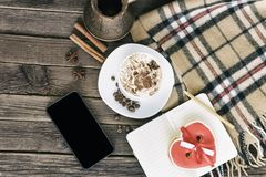 Чашка капучино, сердца сформировала сообщение ширины печений, смартфон и баки кофе на коричневом деревянном столе стоковое изображение rf