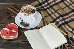 Чашка капучино, сердца сформировала сообщение ширины печений, тетрадь и checkered шотландку на коричневом деревянном столе стоковые фото